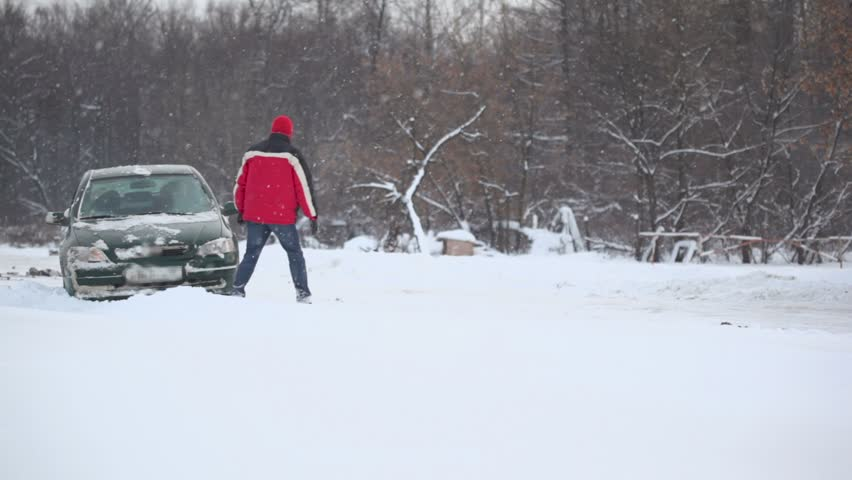 Man and woman tries to release car from snow trap on country road at winter day  - HD stock footage clip