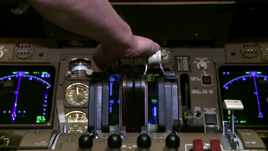 Detail of 747 pilot's hand as he pulls back on jet throttles while plane is on the ground.