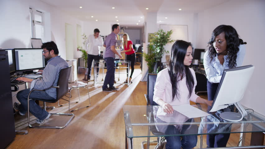 Time lapse clip of casually dressed business men and women in a light and modern open plan office space. Could be a design studio or creative agency.