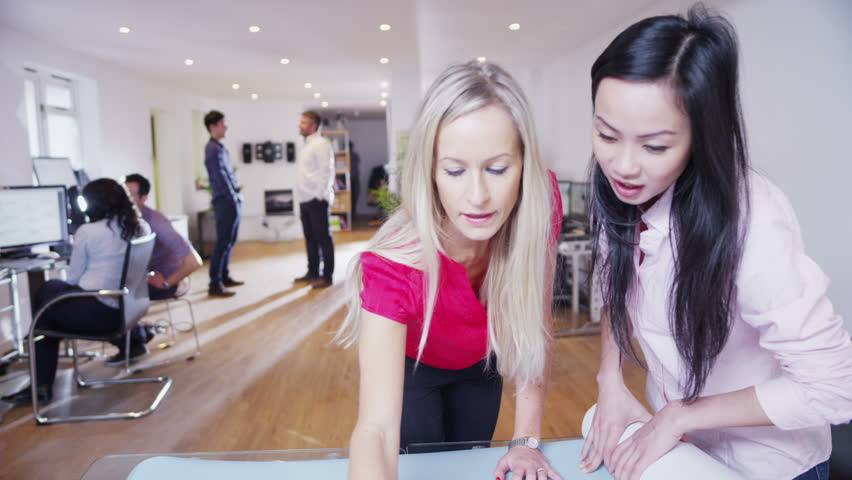 Two beautiful multi-ethnic businesswomen are working in a light and modern office and looking at a map of the world. They are discussing possibilities for future business ventures. In slow motion.