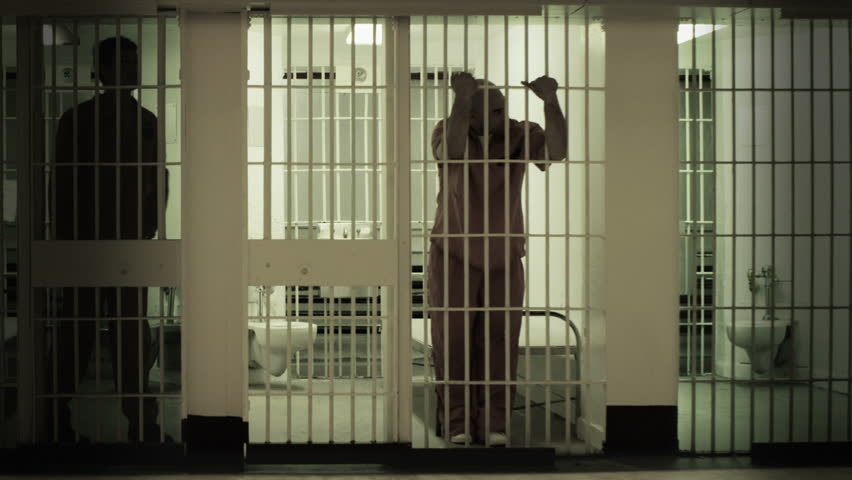 Inmate standing at the bars of his prison cell. Neighboring inmate can be seen in next cell. Desaturated color.