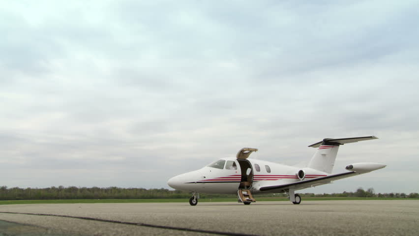 High powered business executive walks to a personal jet and gets on. Wide shot from rear.