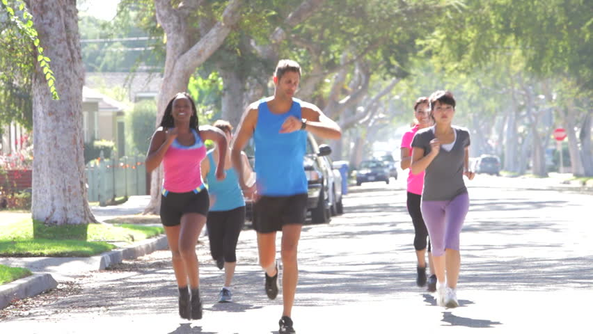 Trainer encouraging group of women as they run on urban street. Shot on Canon 5d Mk2 with a frame rate of 30fps