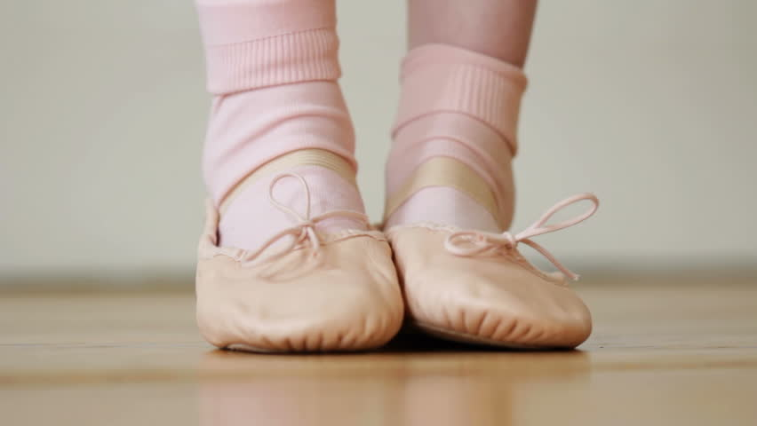 Child's ballet shoes - Rack focus as a little girl points her toe forward in pink leather ballet shoe