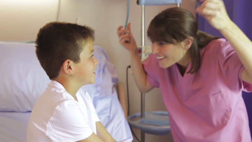 Nurse greets boy sitting on bed before asking him to take breaths and listening through stethescope. Shot on Canon 5d Mk2 with a frame rate of 30fps - HD stock footage clip
