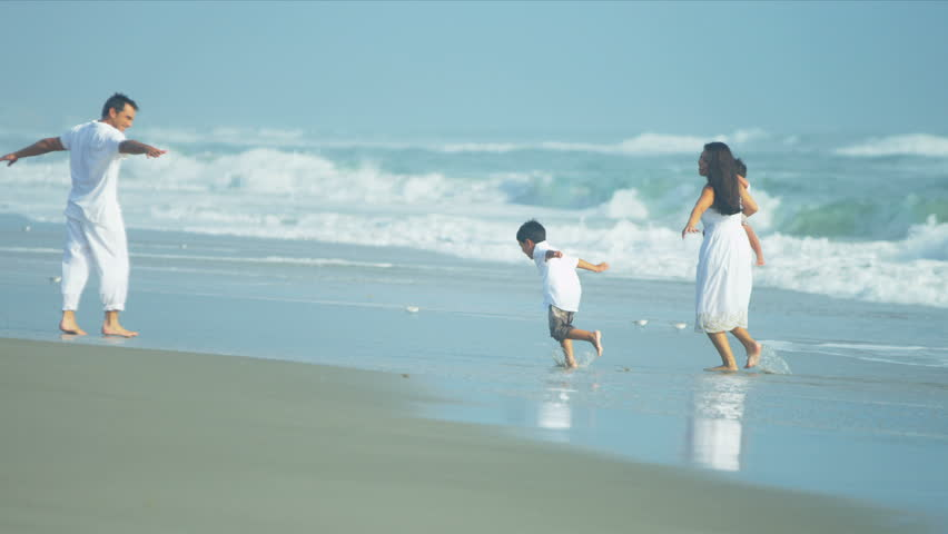 Hispanic young loving family spending vacation on beach playing in the ocean surf shot on RED EPIC - HD stock video clip