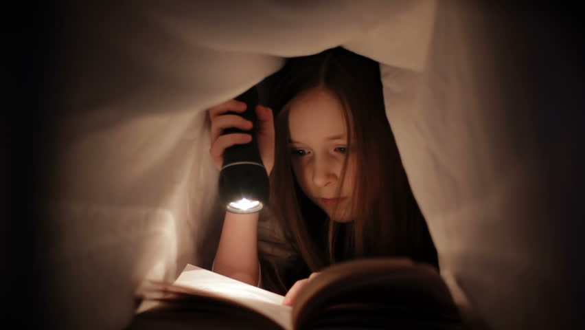 Child Reading in Bed - Little girl reading by torch light under the bed sheets