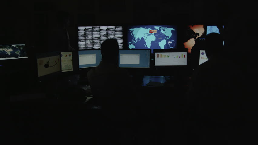 A team of male security personnel working within a busy system control room. This could be a weather station/airport traffic control room. It could be a  power station or police/army control facility.