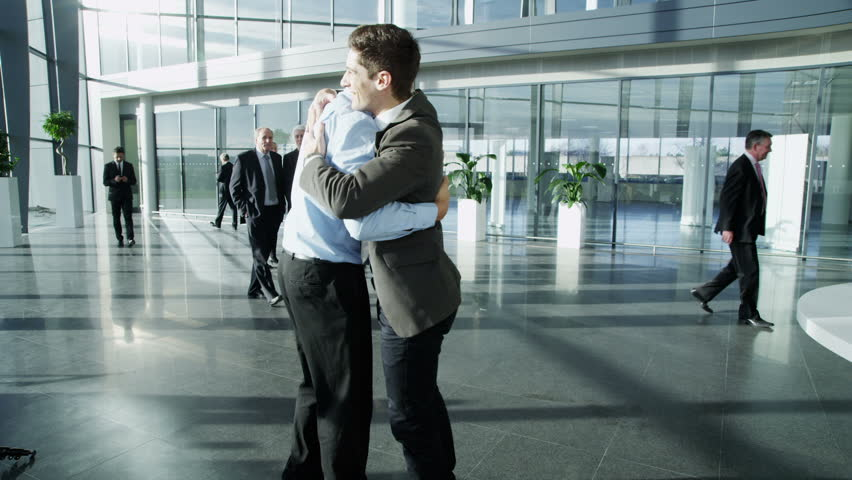 Two confident and attractive young businessmen meet and shake hands in a busy modern office building. In the background other workers can be seen walking around the building. In slow motion.