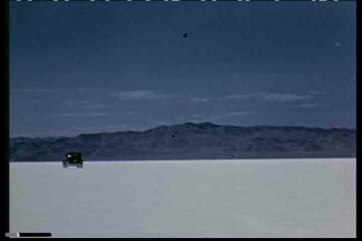 1930s - A car drives along a road near Salt lake City, Utah in the 1930' and across the salt flats. - SD stock video clip