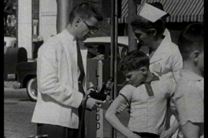 1960s - More people & kids get immunized as various locations across the city. - SD stock footage clip