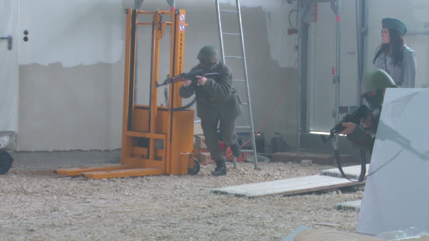 Female officer training with soldiers in warehouse