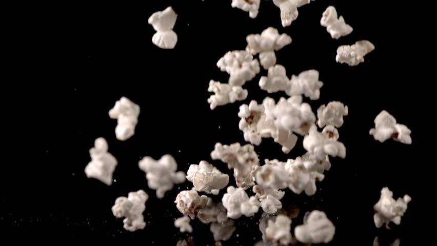 White fluffy pieces of popcorn fall in slow motion against a black background and bounce off each other.