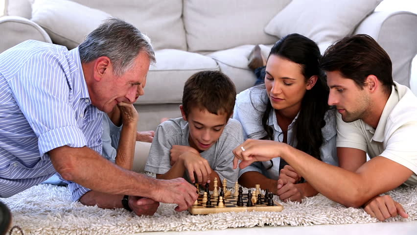 Extended family playing chess at home on the living room floor - HD stock footage clip