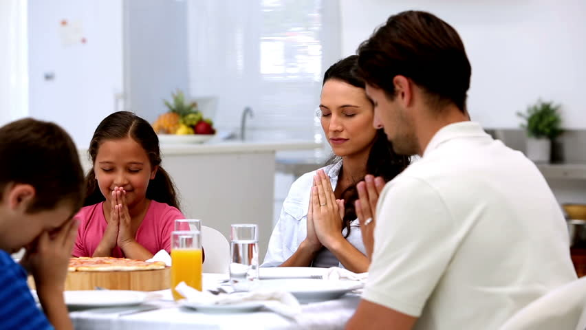 Family saying grace before dinner at home in kitchen