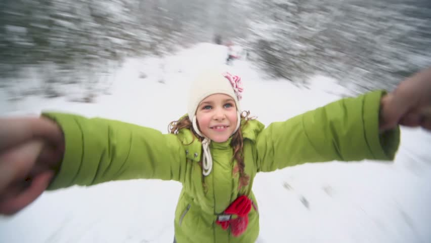 Hand holds little girl which flies above snow at background of winter forest - HD stock footage clip
