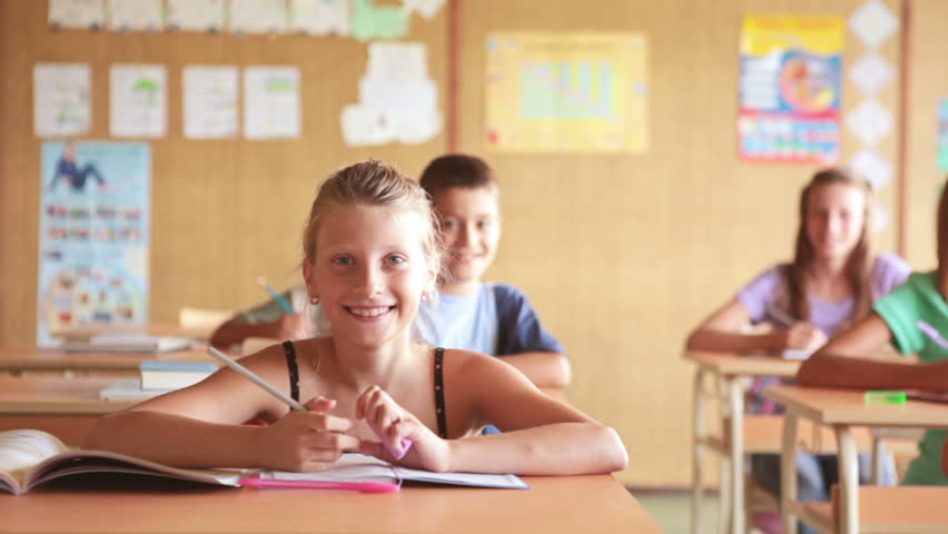 Smiling children sitting at their desks at school and writing. - HD stock footage clip