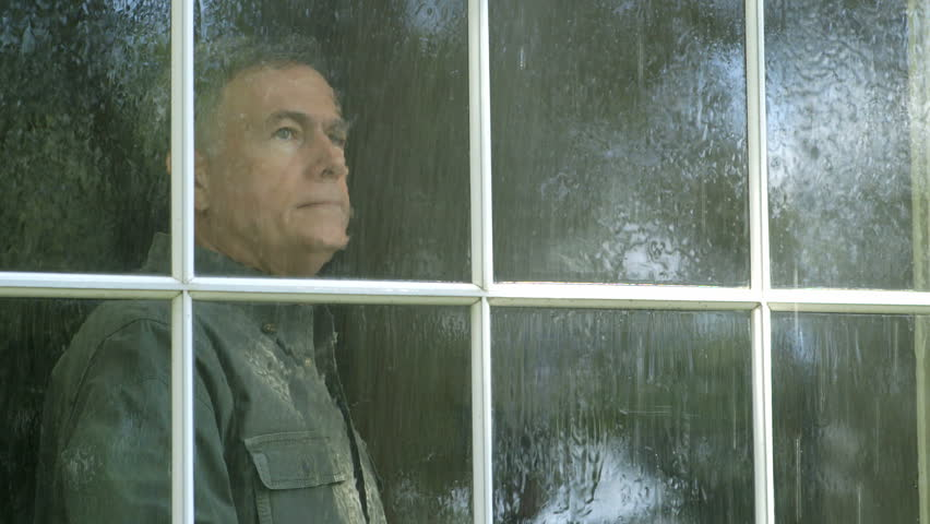 A pensive mature man watches a summer rain shower from his living room window. - HD stock footage clip