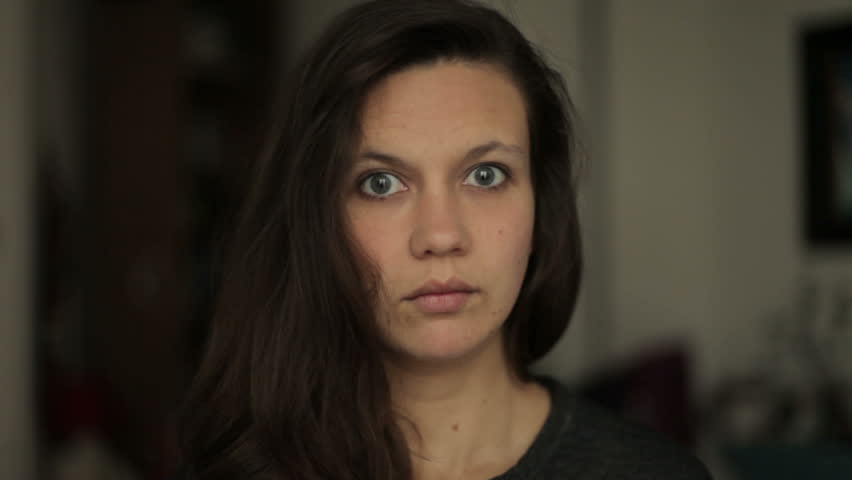 A young beatiful woman is looking directly in camera. She looks shocked and surprised by something she sees in front of her.