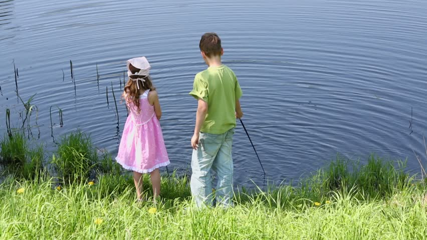 Young love a cute little girl kisses a little boy on the for Little girl fishing pole