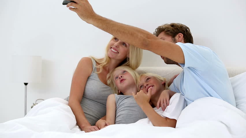 Father taking self portrait of him with happy family at home in bed - HD stock video clip