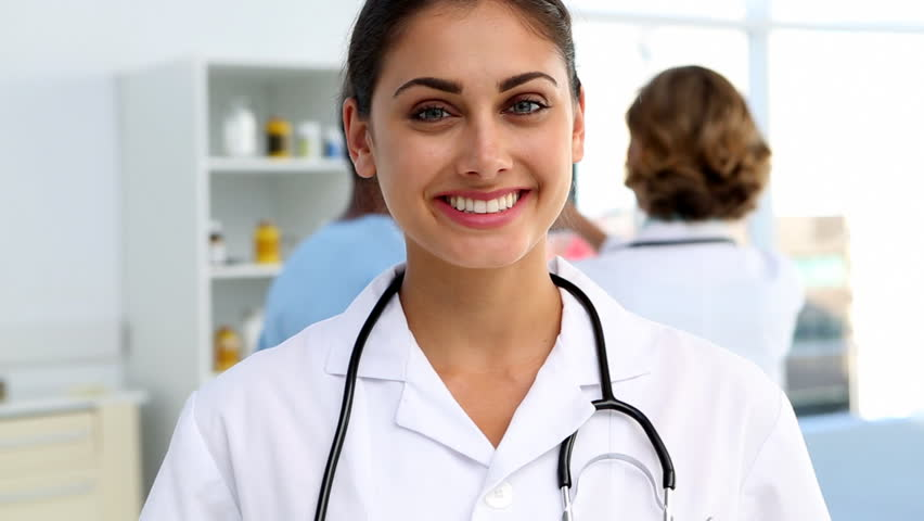 Doctor standing and smiling in front of medical team analysing x-ray