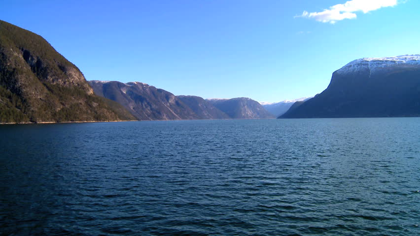 Mountains & crystal clear water of a glacial fjord in Norway