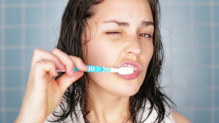 healthy young woman brushing teeth in bathroom waking up portrait