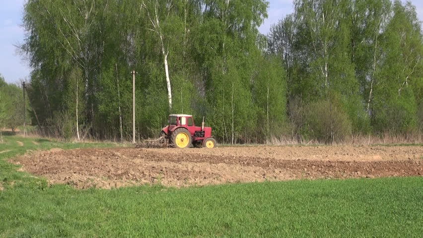 agriculture tractor plowing spring farm field  - HD stock video clip