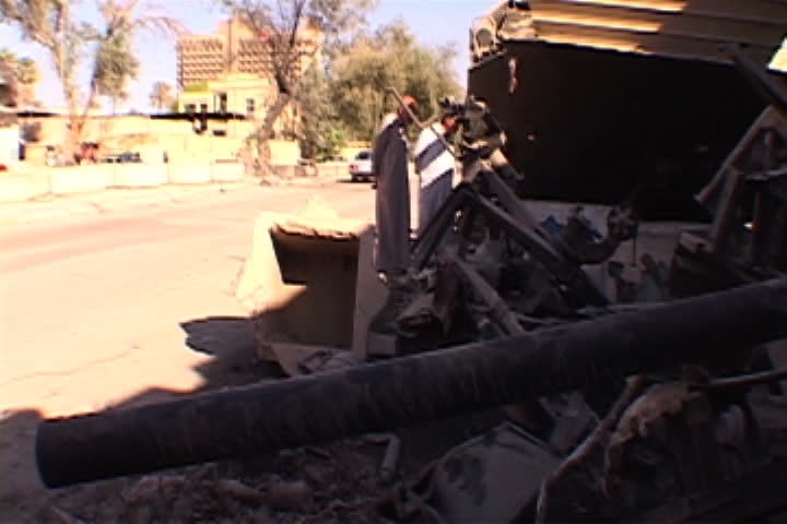 BAGHDAD, IRAQ - APRIL 29, 2003: Pile of debris from bombed building, a few passersby look at the rubble.