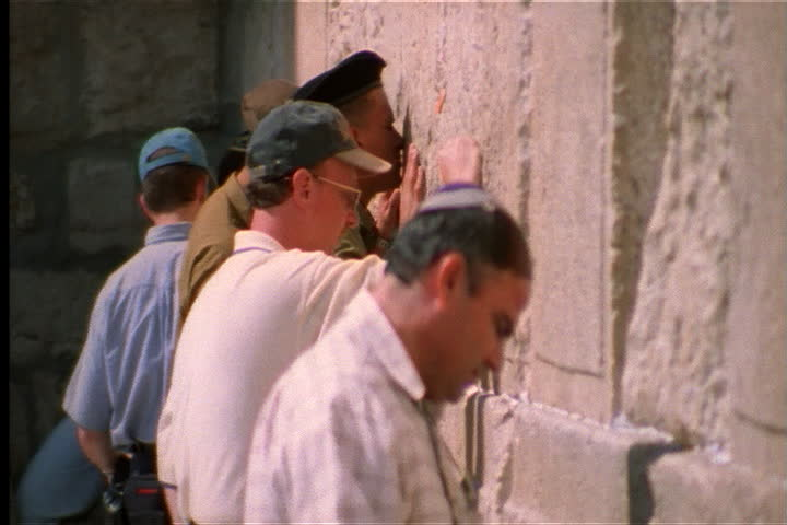 JERUSALEM, ISRAEL - JULY 01, 2000: Young soldier joins others against Western Wall, he whispers something and kisses it. - SD stock video clip