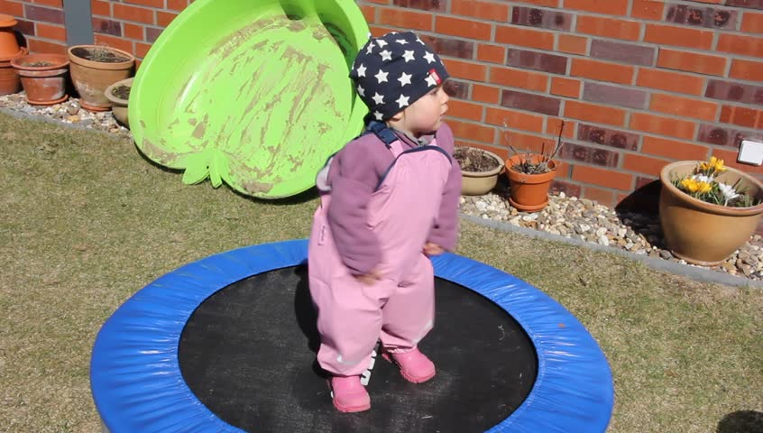 Little girl (one year and five months old) is trying to jump on the trampoline - HD stock footage clip