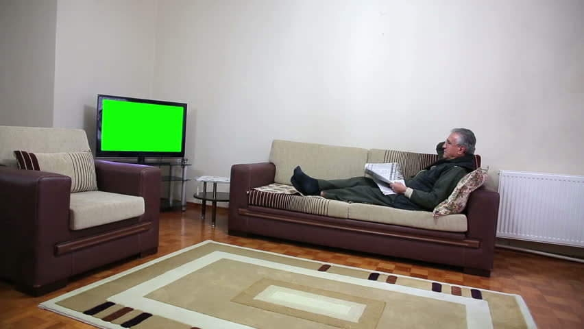 Senior Man Watching Tv Show While Sitting On Sofa In His