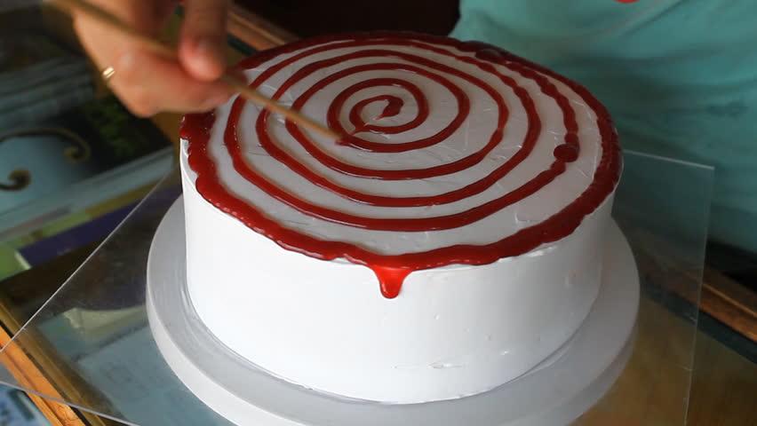Baker decorating vanilla cake with strawberry sauce #4111408