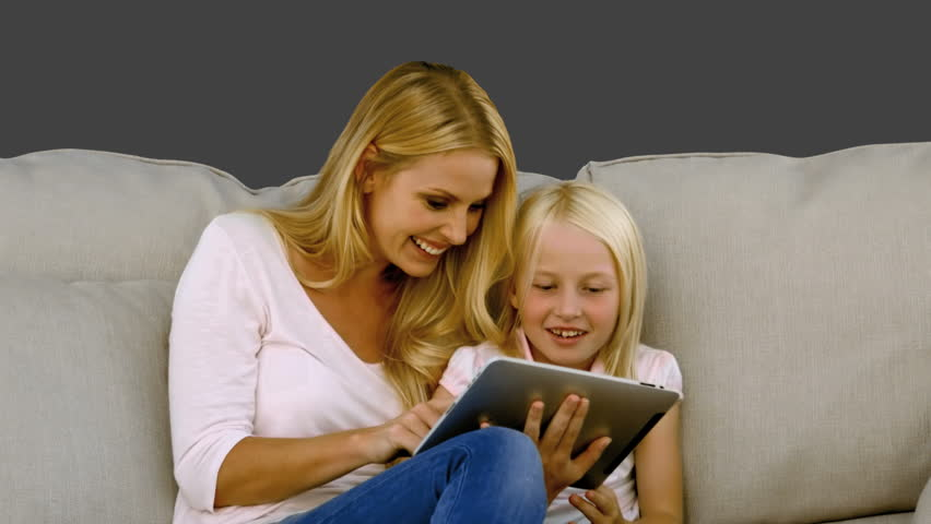 Mother and her daughter using digital tablet on sofa in slow motion on grey screen - HD stock video clip