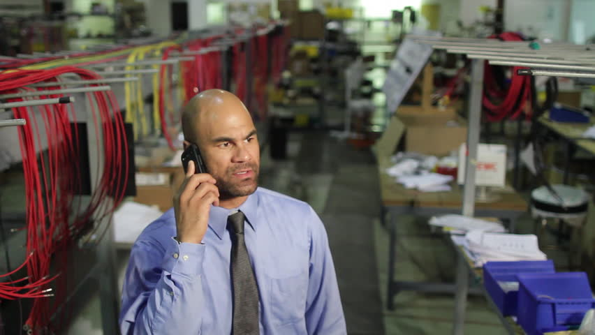 Business man on happy phone call in industrial setting.