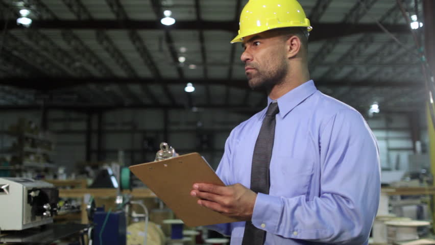 Business man checks inventory in an industrial warehouse setting, then turns and