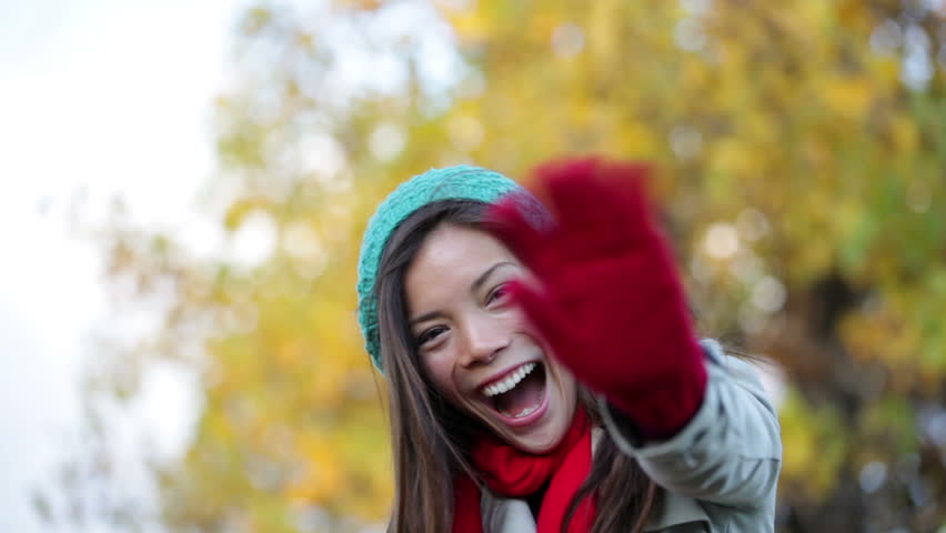 Fall woman waving hello and blowing a kiss in beautiful autumn foliage forest. Happy smiling mixed race asian caucasian girl saying hi looking at camera outdoors.