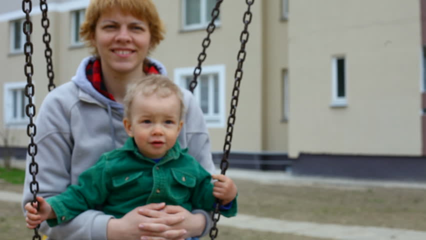 mother and child play on swing on the playground - HD stock video clip