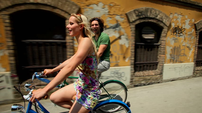 Couple cycling in town on sidewalk lane past old abandoned building  | Shutterstock HD Video #4153933