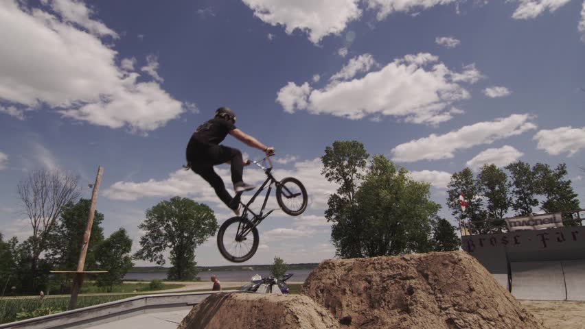 BMXer Dirt Jump Trick on Sunny Day - HD stock footage clip