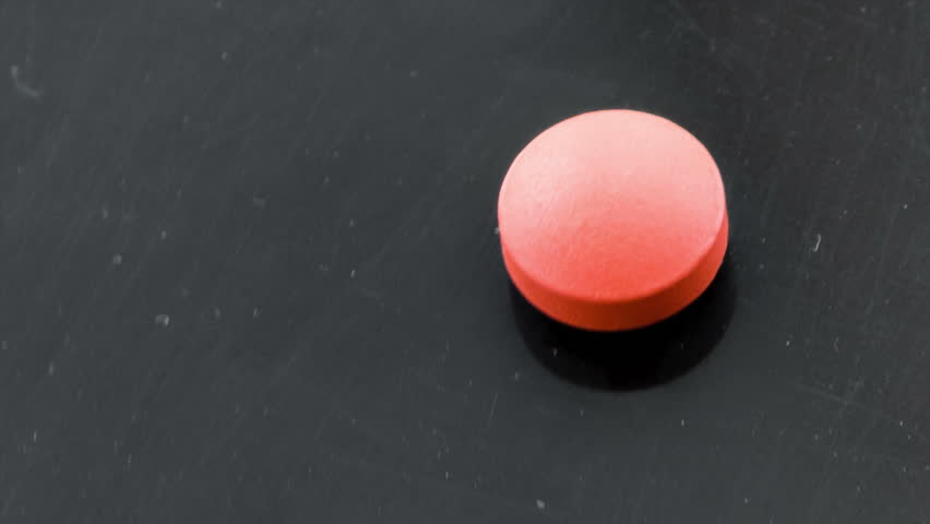 Medical pills placed on rotating table, shot with black background