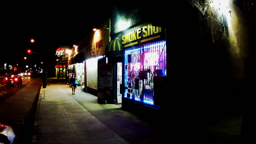 LOS ANGELES, CA: April 18, 2013- Women walking past a brightly lit smoke shop at night circa 2013 in Los Angeles. A good generic shot to fill out any marijuana or tobacco related story.