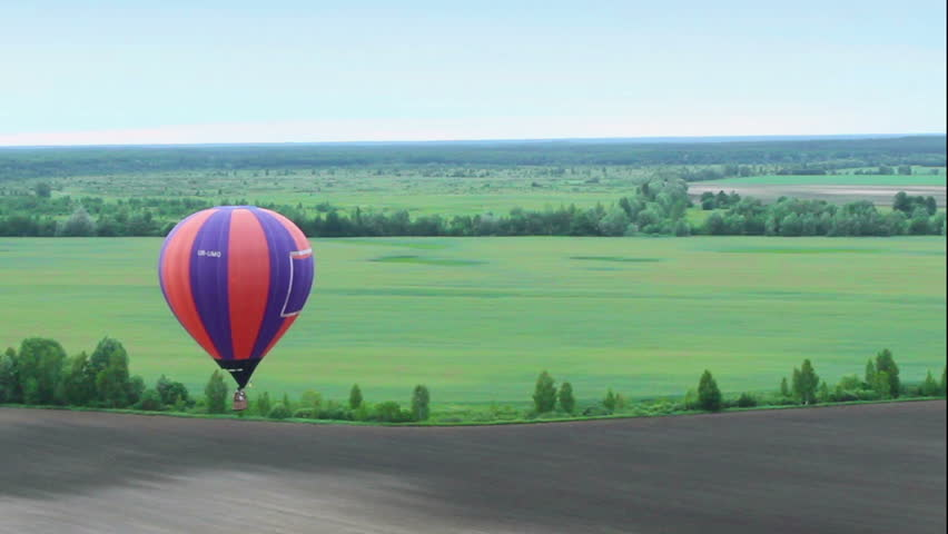 Blue horizon aerial shot from hot air balloon pov. Flying over suburb, fields