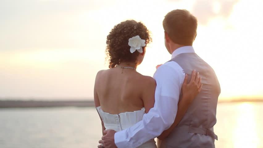 Newly wed couple watch sunset