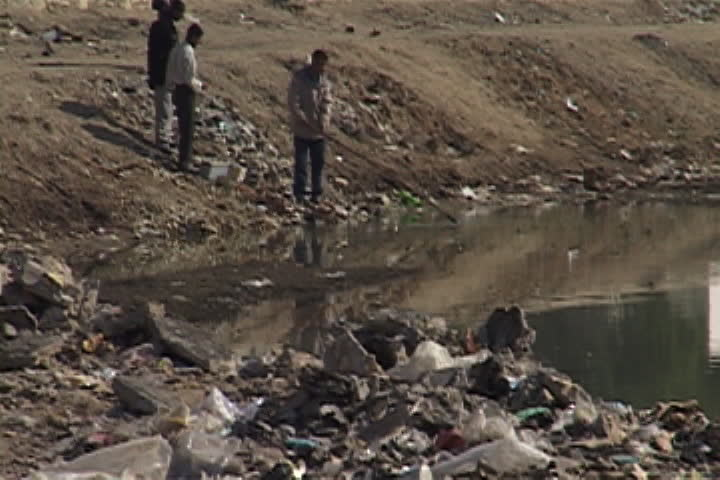 NASIRIYAH, IRAQ - DECEMBER 14, 2003: Three men on the banks of the Euprates River surrounded by piles of trash and debris. One is attempting to fish something out of the water with a pole.