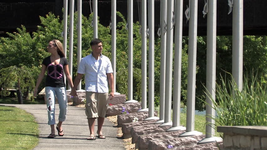 A young couple walk in the park on a sunny day. - HD stock video clip