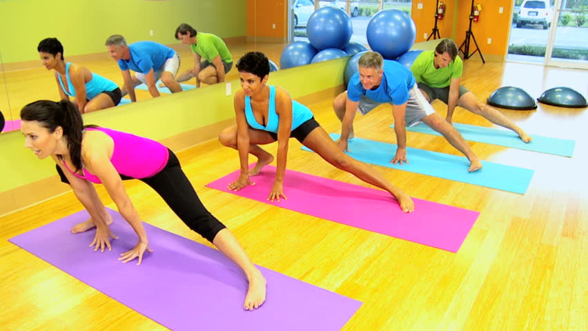 Caucasian female fitness instructor with multi ethnic class using mats for floor exercises - HD stock footage clip