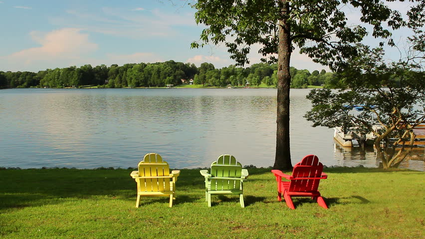 three colorful adirondack chairs overlook a sparkling lake with a boat
