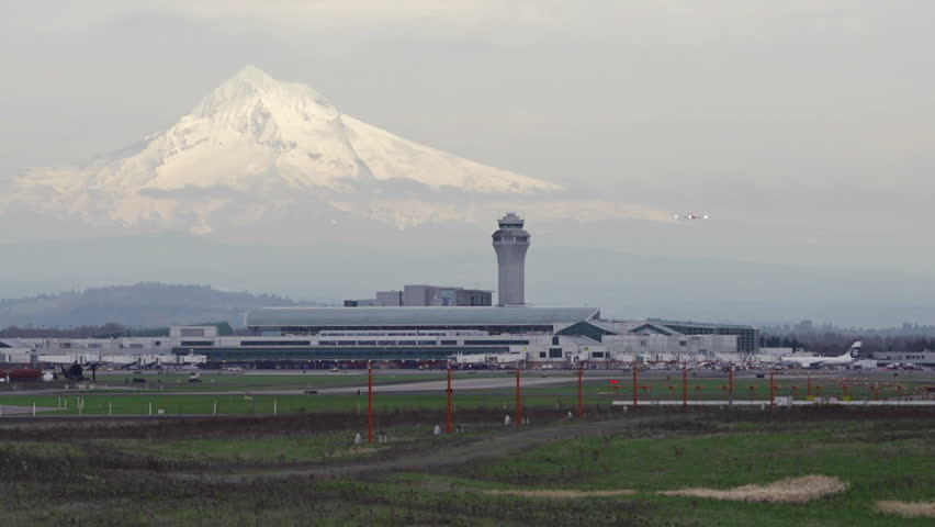 PORTLAND, OR  - A twin-engine commuter plane lands at Portland International Airport, with Mt. Hood looming in the background, in Portland, Oregon
